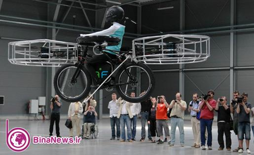 Journalists attend a presentation of a flying bicycle, carrying a dummy, at Letnany's fair hall in Prague